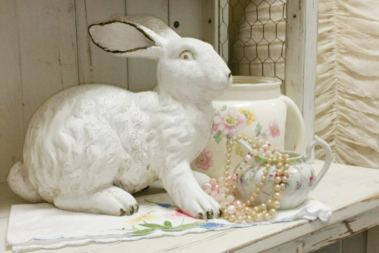 Easter bunny beside floral pitcher.